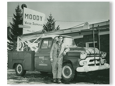 James Moody the founder of Moody and Associates groundwater and environmental professionals since 1891 standing next to old pickup truck outside of water supply company store work for the company now in Houston PA