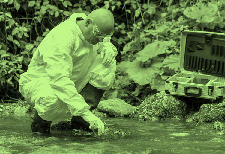 Moody employee man working to obtain water samples in blue running stream surrounded by green leaves in environment