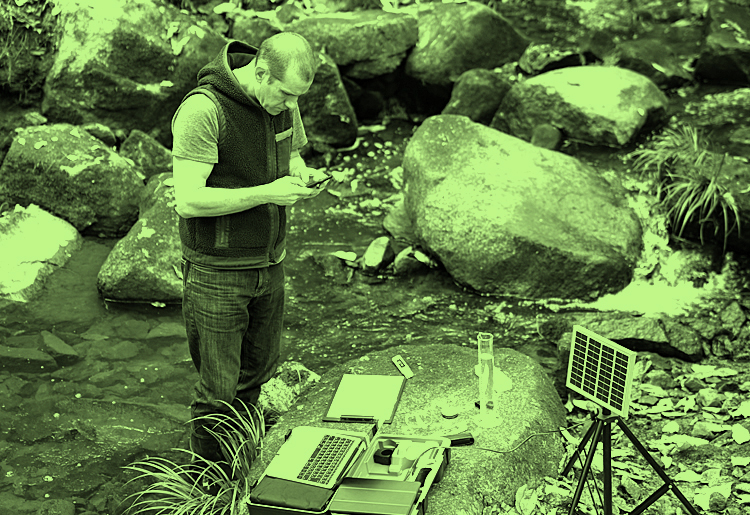 Moody blue water ecological permitting block man employee examining water and rocks with advanced geological tools