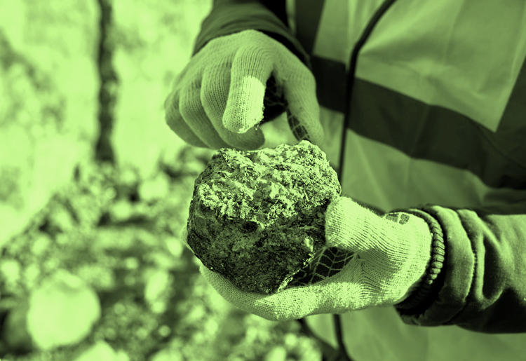 Moody and Associates, Inc. Fill Management Services environmental man holding big brown soil and rock wearing gloves